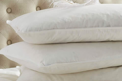 dry cleaned feather pillows stacked on each other